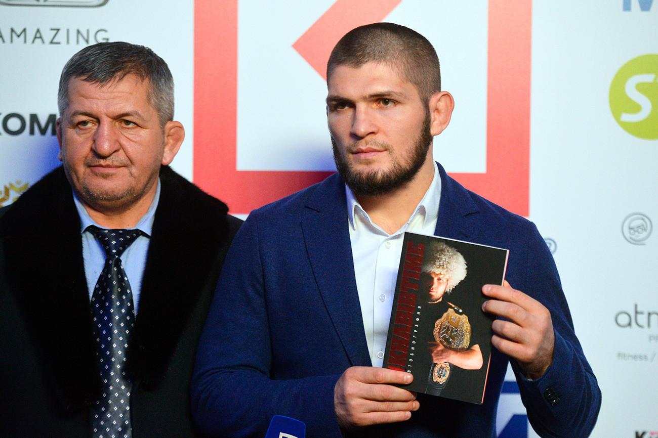 """Шампионот на УФС во лесна категорија Хабиб Нурмагомедов (десно) на презентација на својата автобиографска книга """"Времето на Хабиб""""."""