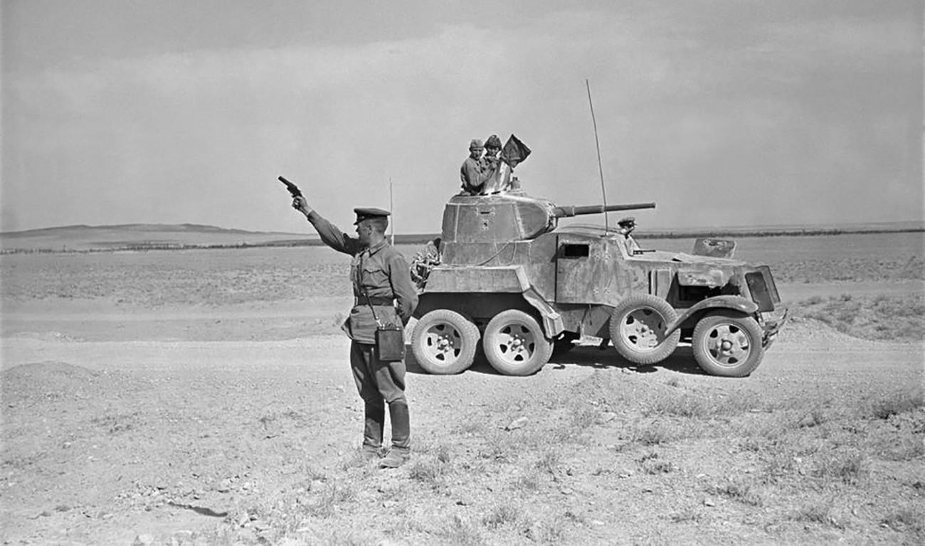 Oficial militar soviético ergue pistola sinalizadora no deserto iraniano