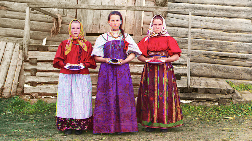 Young Russian peasant women in front of traditional wooden house, in a rural area along the Sheksna River near the small town of Kirillov. Early color photograph from Russia, created by Sergei Prokudin-Gorsky as part of his work to document the Russian Empire from 1909 to 1915.