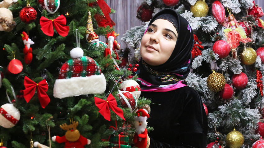 GROZNY, RUSSIA - DECEMBER 13, 2018: A Muslim woman shopping for Christmas ornaments for sale ahead of Christmas and New Year's Eve. - - -