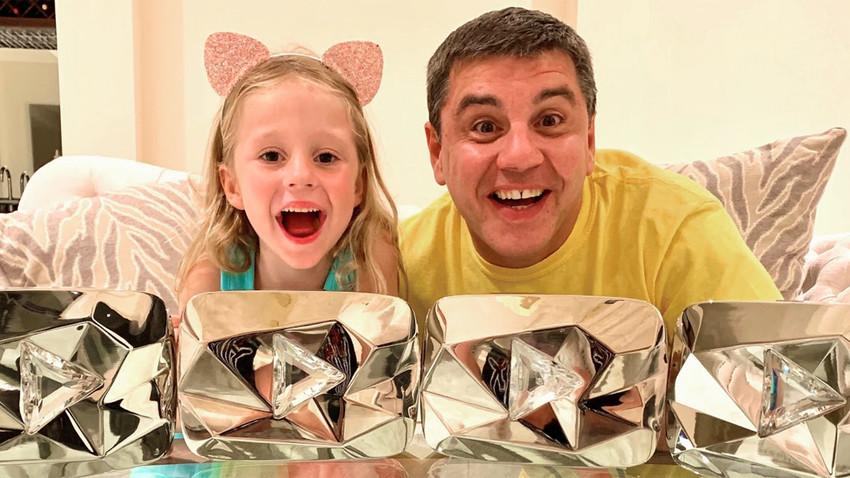 """Anastasia e o pai com seus quatro prêmios  do YouTube """"Diamond Creator Awards""""."""
