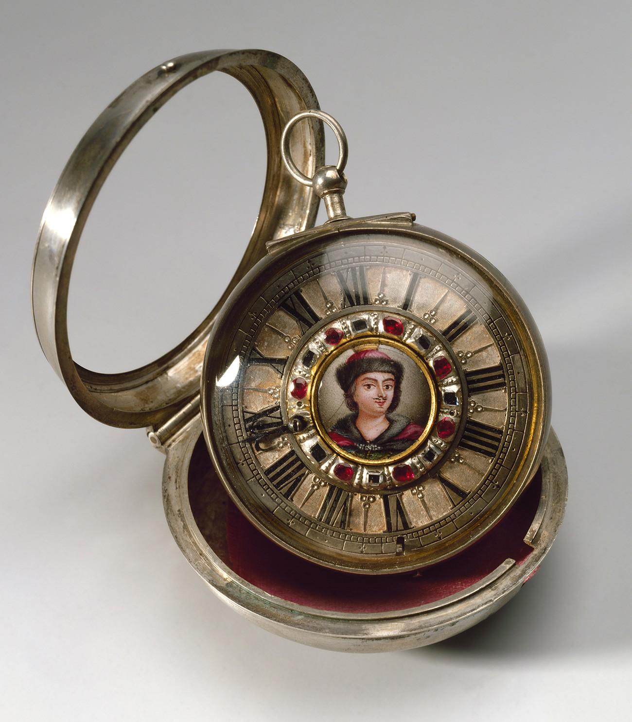 ЧАСОВНИК У ДВОСТРУКОМ КУЋИШТУ  Лондон (?), почетком 18. века, израда: Пол Лулен    Легуре бакра, челик, полирани челик, сребро, емајл, дијаманти, рубини, позлата, пресовање, стакло, свила