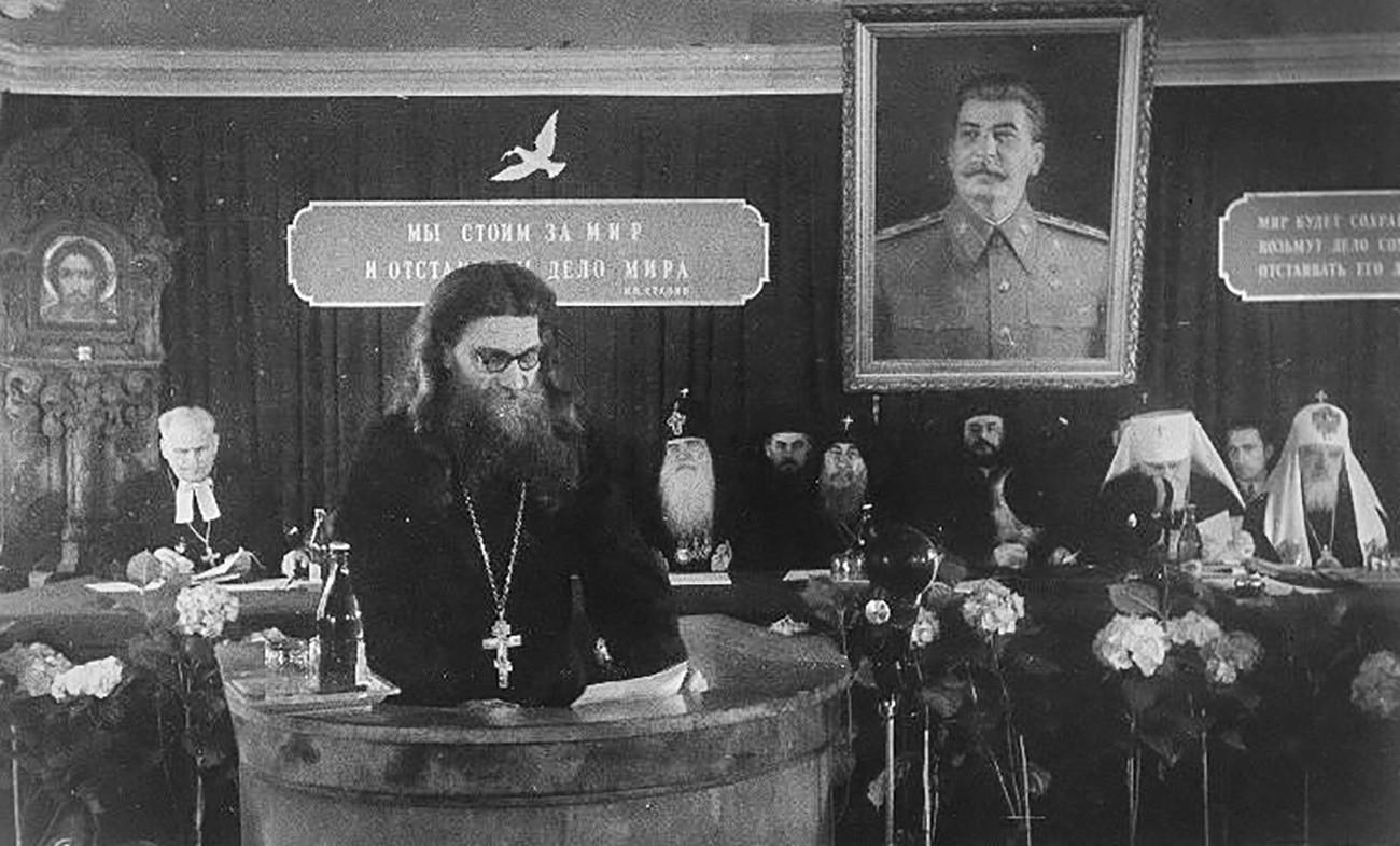 Seorang pendeta memimpin rapat di bawah potret Stalin, 1940-an.