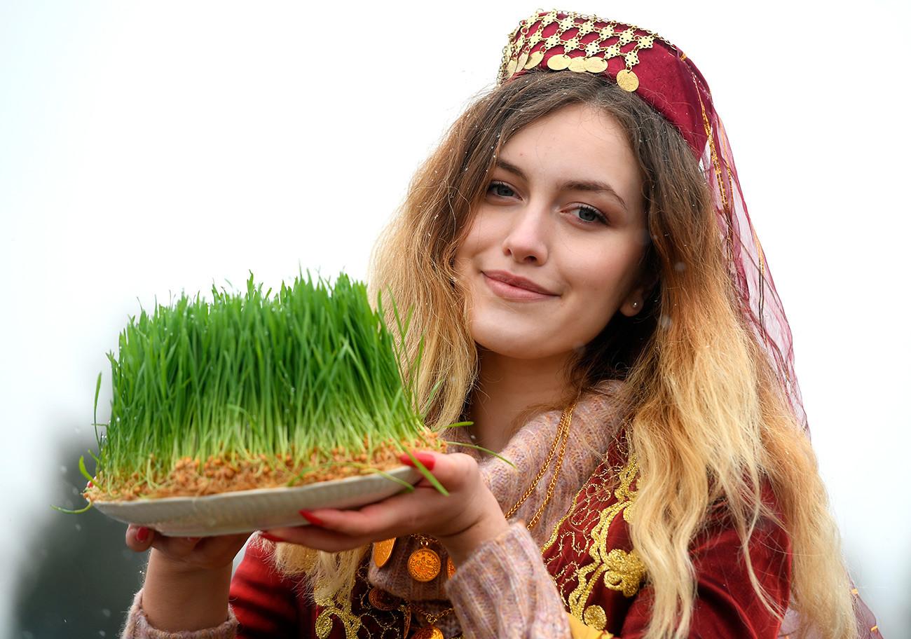 """Девојка са посудом """"сумуљак"""" од проклијале пшенице (посађене 15 дана пре празника) на прослави Навруза у Казању."""