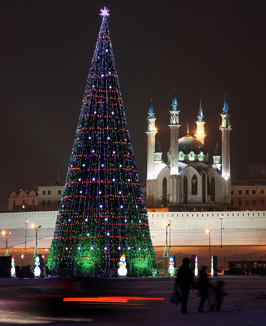 People pass by a New Year's tree, with the Kul Sharif Mosque in the background, in the Russian city of Kazan.
