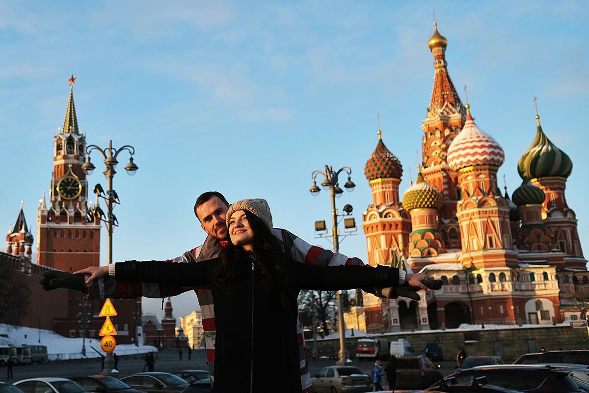 Turisti poziraju ispred Spaske kule i Hrama Vasilija Blaženog u pozadini. Moskva, Rusija.