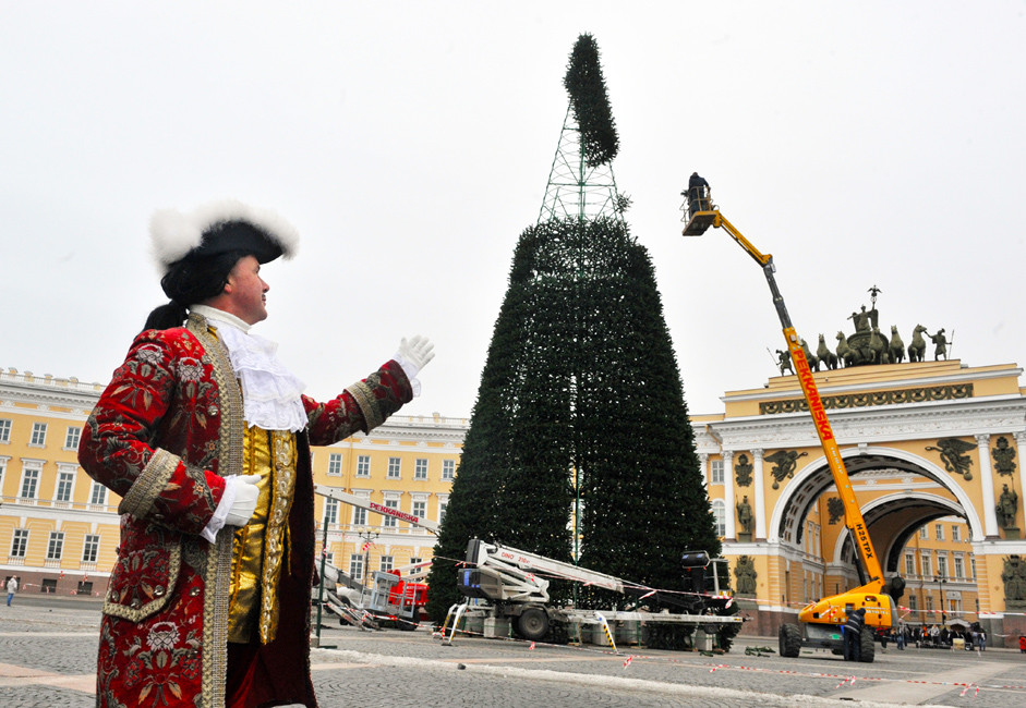 Guindastes são usados para montar a celebrada árvore de Natal da Praça do Palácio, em São Petersburgo, onde atores durante todo o ano se vestem de figuras históricas como Pedro, o Grande (esq.) para entreter os turistas.