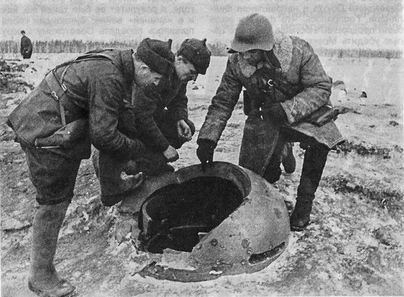 Група црвеноармејаца разгледа оклопни поклопац на финском бункеру.