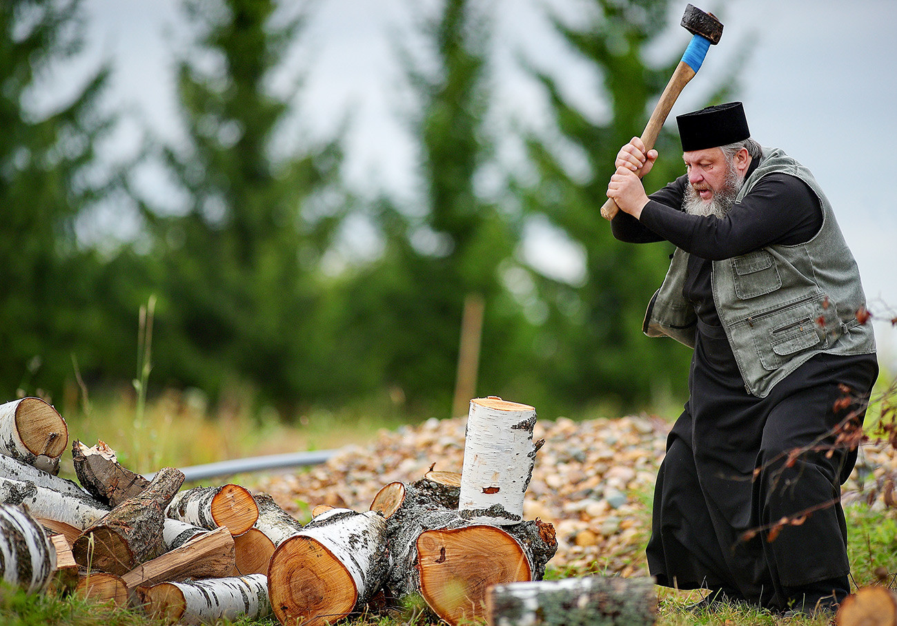 Le prêtre Vladimir Smaglov est en train de couper du bois dans la cour de sa maison. Région d'Ivanovo, ville de Kinechma.