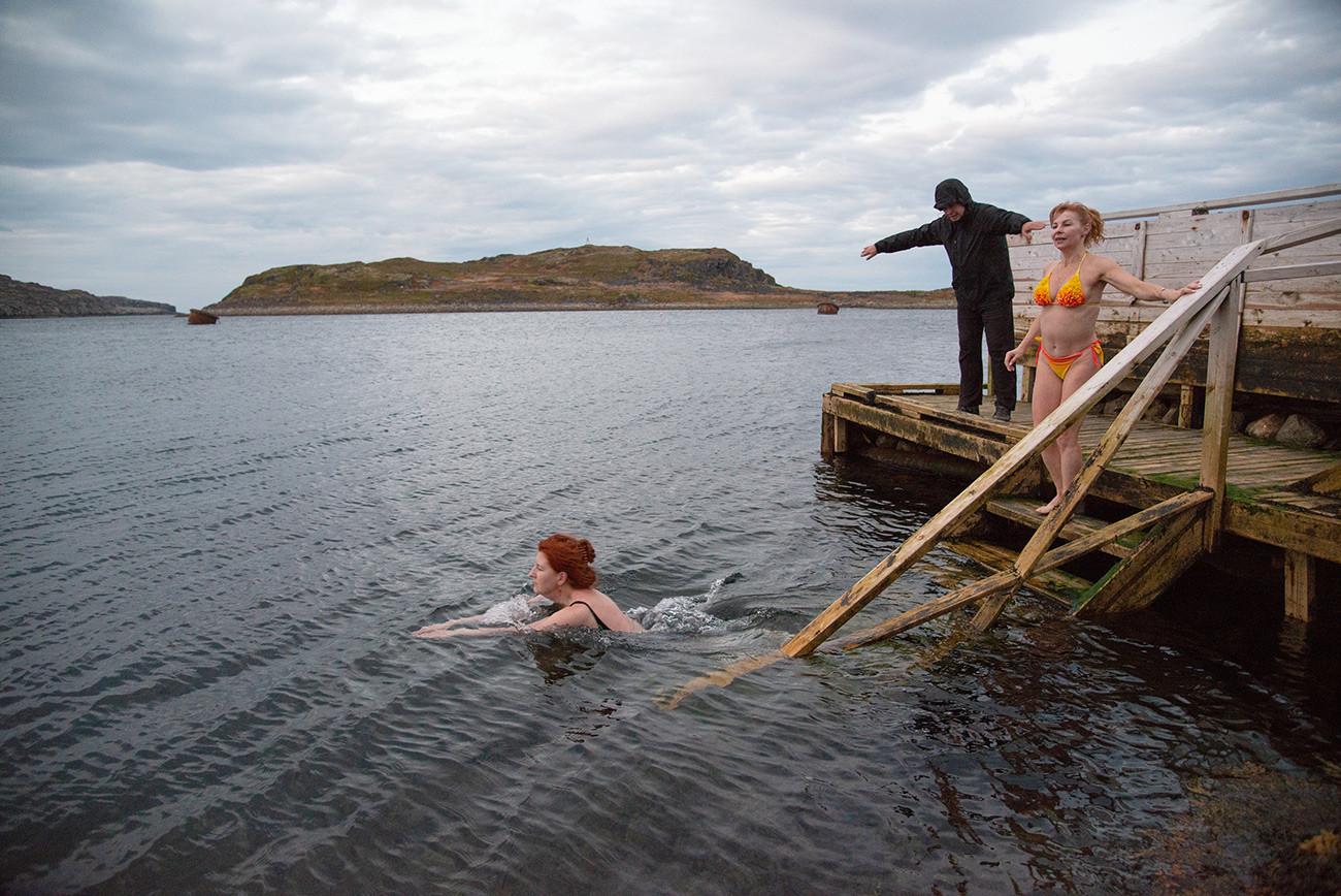 Elena Glazounova, une touriste moscovite, et la locale Lioudmila Sobolevskaïa, se baignent dans la mer de Barents après le bania (sauna russe). La température de l'eau est d'environ -5°. Région de Mourmansk, village de Dalnyé Zelentsy