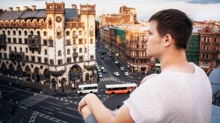 Seorang pemuda duduk di atap dan melihat ke Ploshchad Lva Tolstogo di Sankt Peterburg, Rusia.