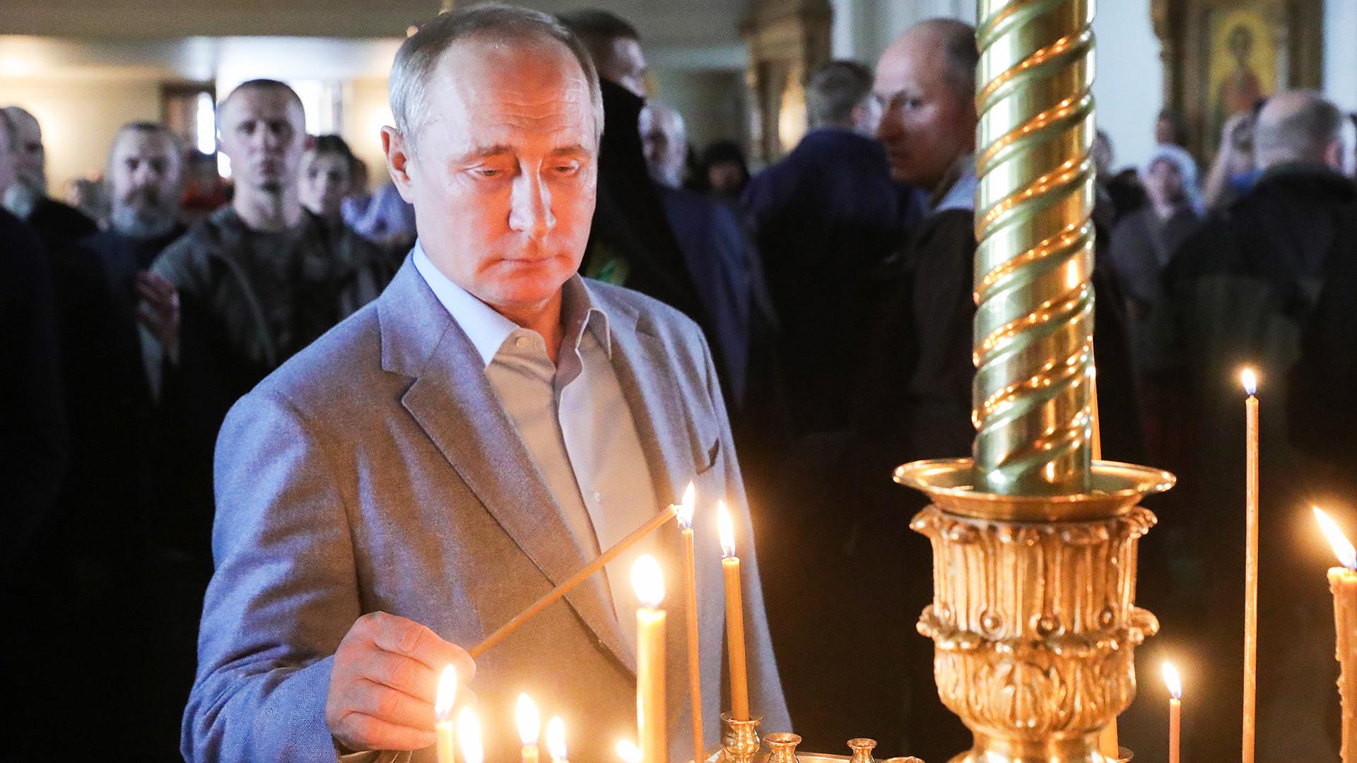 Le président russe Vladimir Poutine allume une bougie lors de sa visite au monastère de Valaam en Carélie (Nord-Ouest de la Russie), 2019