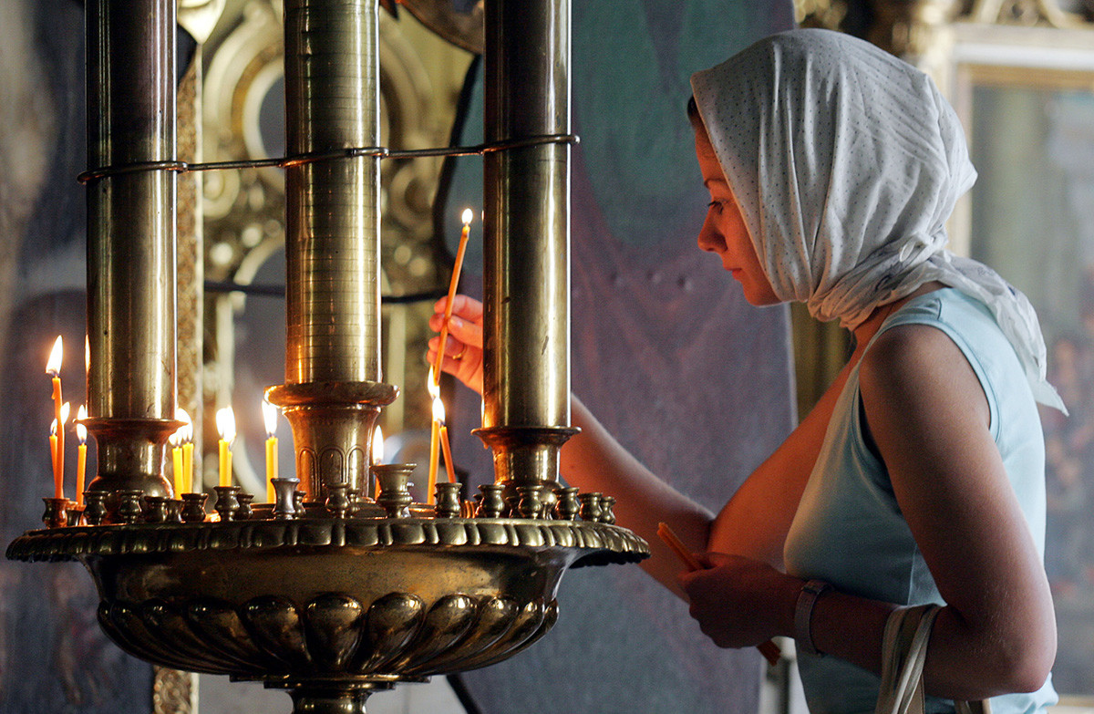 Russian woman lights a candle during a remembering church service in Moscow