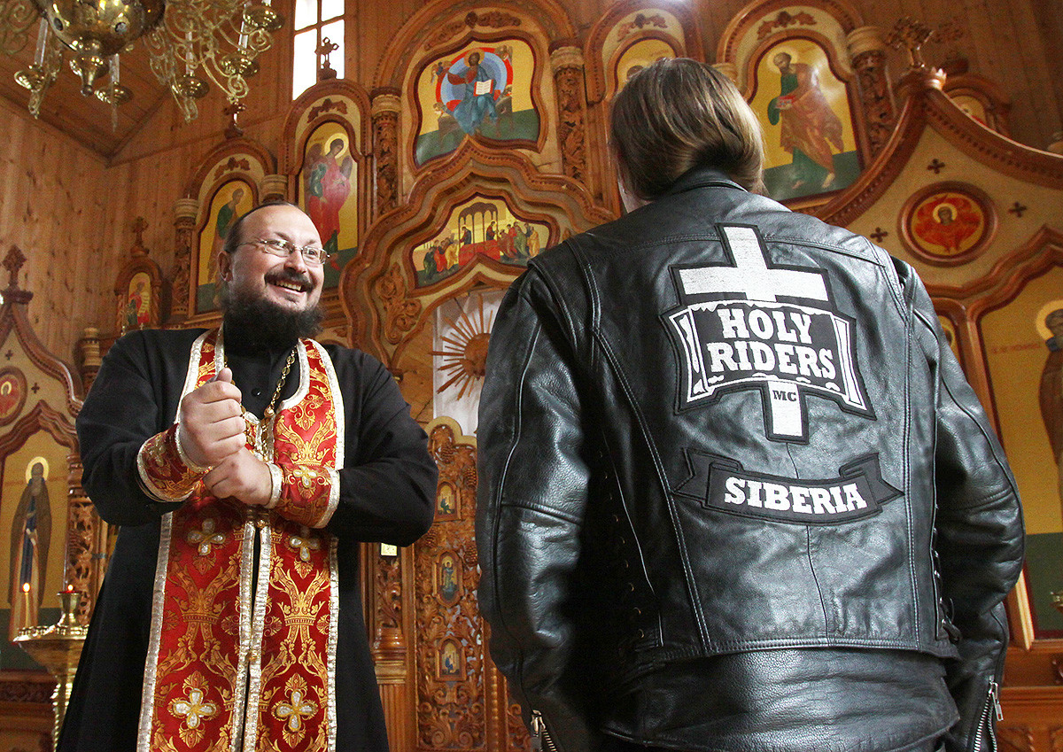 Russian Orthodox priest Father Alexander (L) speaks with a biker at a church in Kemerovo on July 31, 2010. Father Alexander, himself an avid biker, makes several religious biker pilgrimages a year to various churches in the area