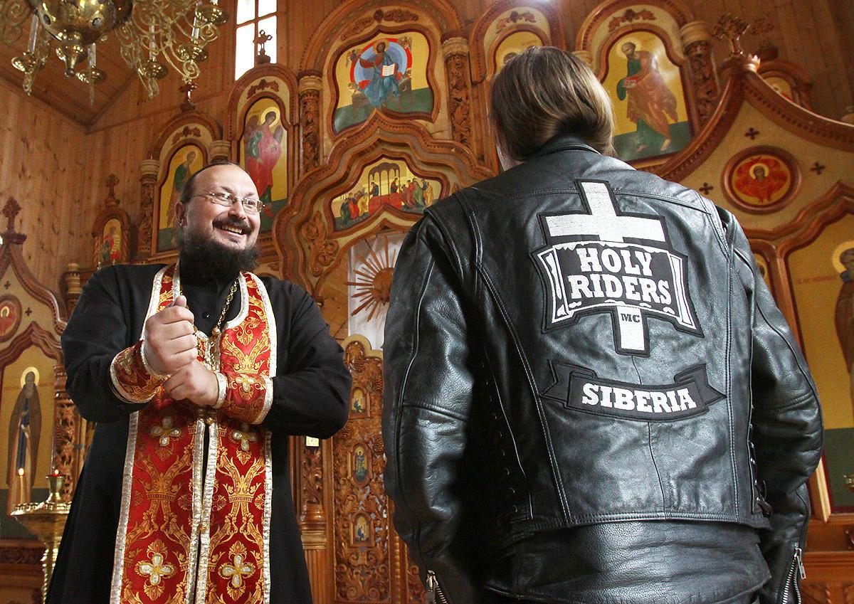 Ruski pravoslavni duhovnik oče Aleksander (L) se pogovarja z bajkerjem v cerkvi v Kemerovu 31. julija 2010. Oče Aleksander, tudi sam navdušen bajker, na leto opravi več verskih bajkerskih romanj v različne cerkve v okolici