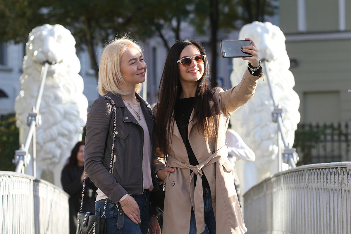 Young women take a selfie on the Lion Bridge (Bridge of Four Lions), a pedestrian bridge across the Griboyedov Canal in central St Petersburg