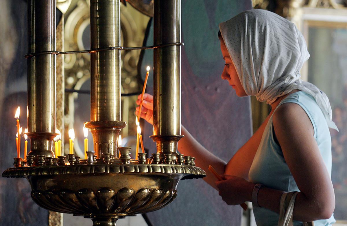 Seorang perempuan Rusia menyalakan lilin saat kebaktian di gereja, di Moskow.