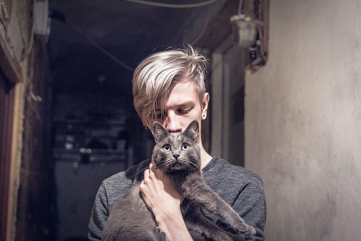 Млада жена са кратком косом држи мачку у свом стану у Санкт Петербургу.