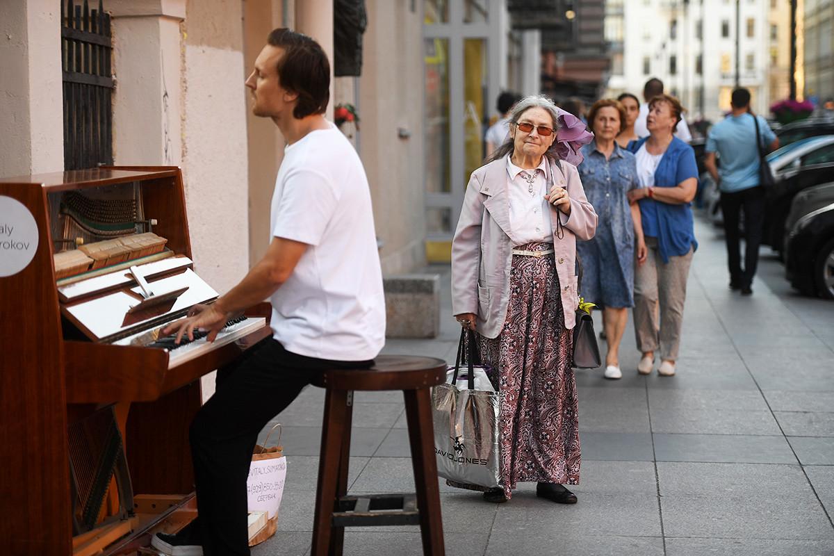 Пролазници слушају наступ уличног музиканта у Санкт Петербургу.