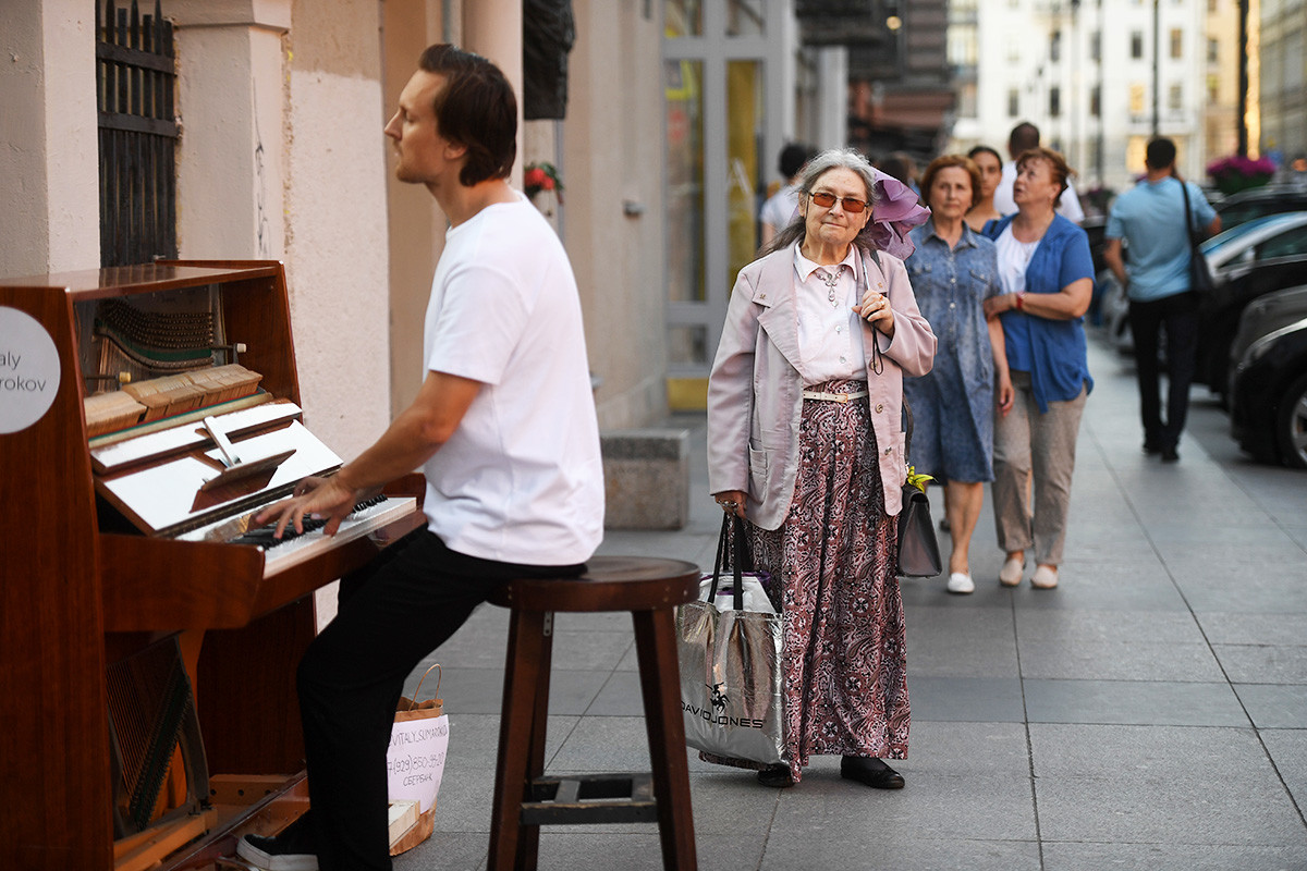 Минувачи слушат изпълнение на уличен музикант в Санкт Петербург