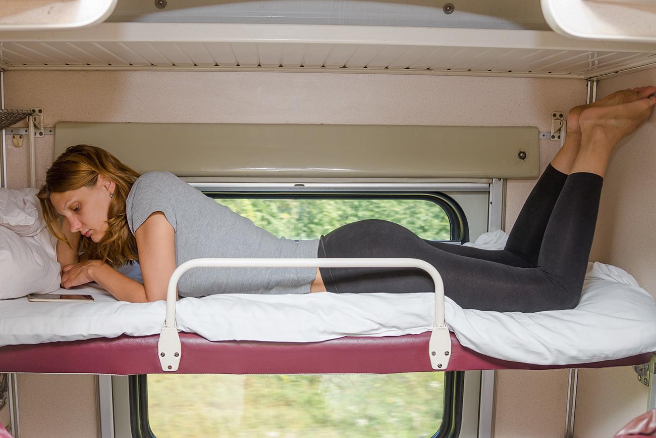 Djevojka u vlaku na gornjem ležaju u plackartnom vagonu gleda u telefon.