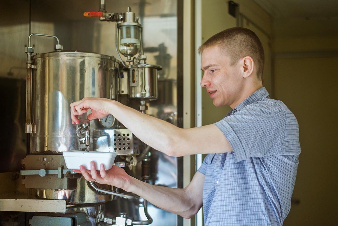 Čovjek s Kavkaza ulijeva vrelu vodu u zdjelu.