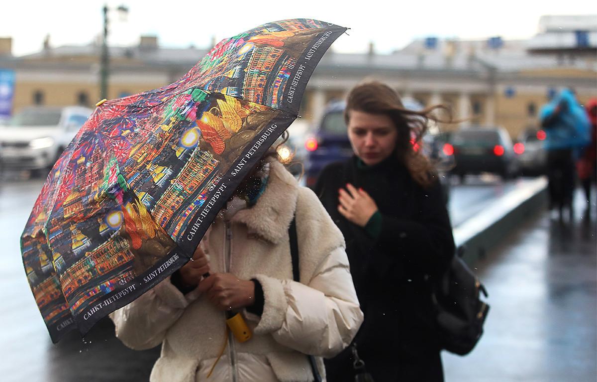 Ljudje v močnem vetru in dežju v centru Sankt Peterburga.