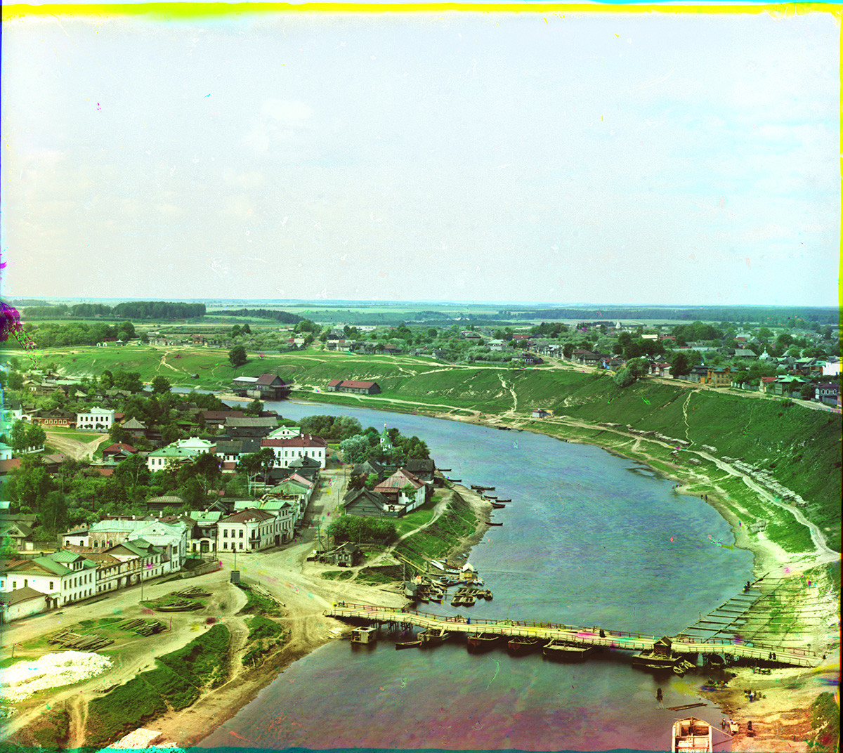 View west up Volga River from Dormition Cathedral bell tower. Middle: Old wooden pontoon bridge with yellow, red & blue smudges indicating movement of horse during three exposures of Prokudin-Gorsky's negative. Left: Prince Dmitry Side. Summer 1910.