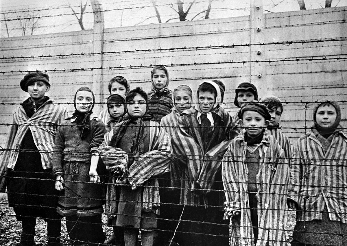 Kinder hinter einem Stacheldrahtzaun im KZ Auschwitz