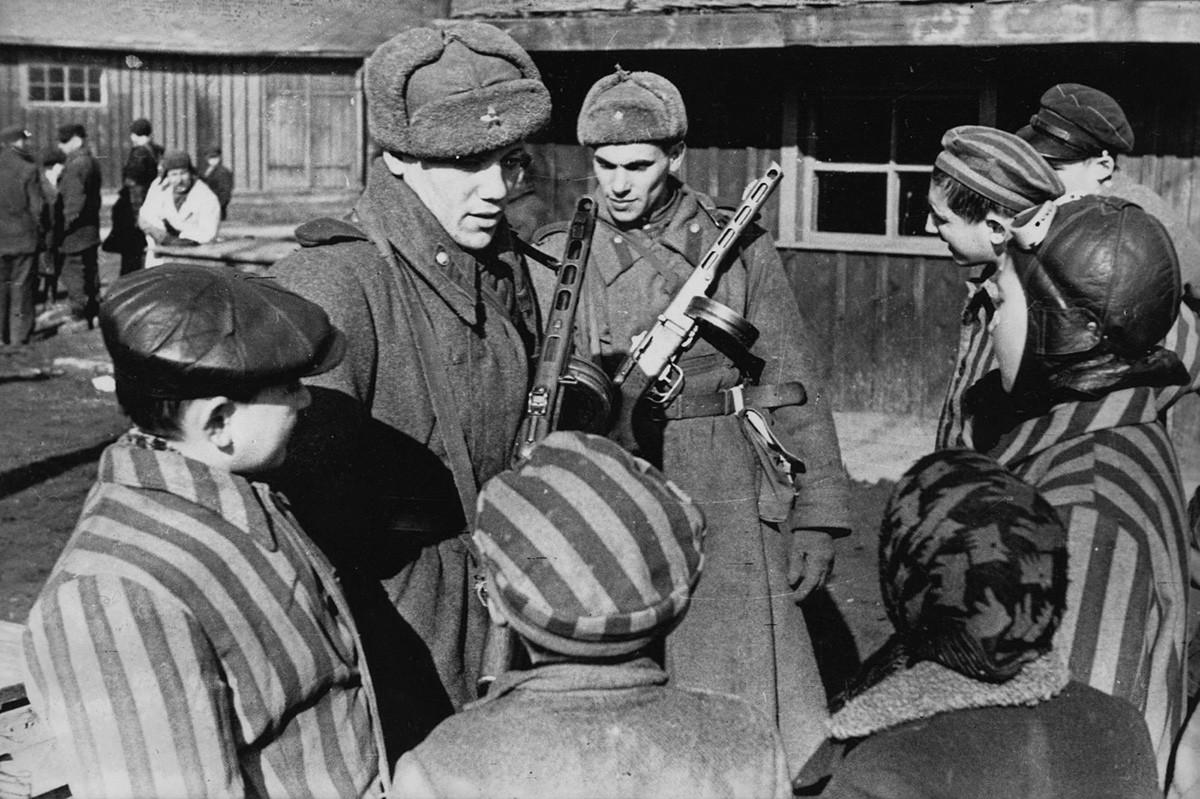Prajurit Soviet mengobrol dengan anak-anak yang baru saja dibebaskan dari Kamp Konsentrasi Auschwitz.