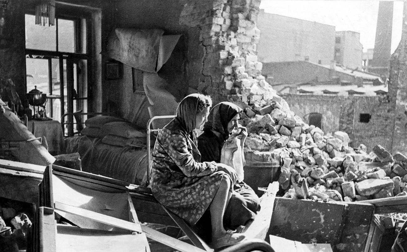 Dua orang perempuan duduk di antara puing-puing setelah Jerman mengebom Leningrad. Demi memaksa para pejuang Rusia menyerah, pasukan Jerman mengebom habis-habisan kota tersebut sehingga menewaskan banyak warga sipil.