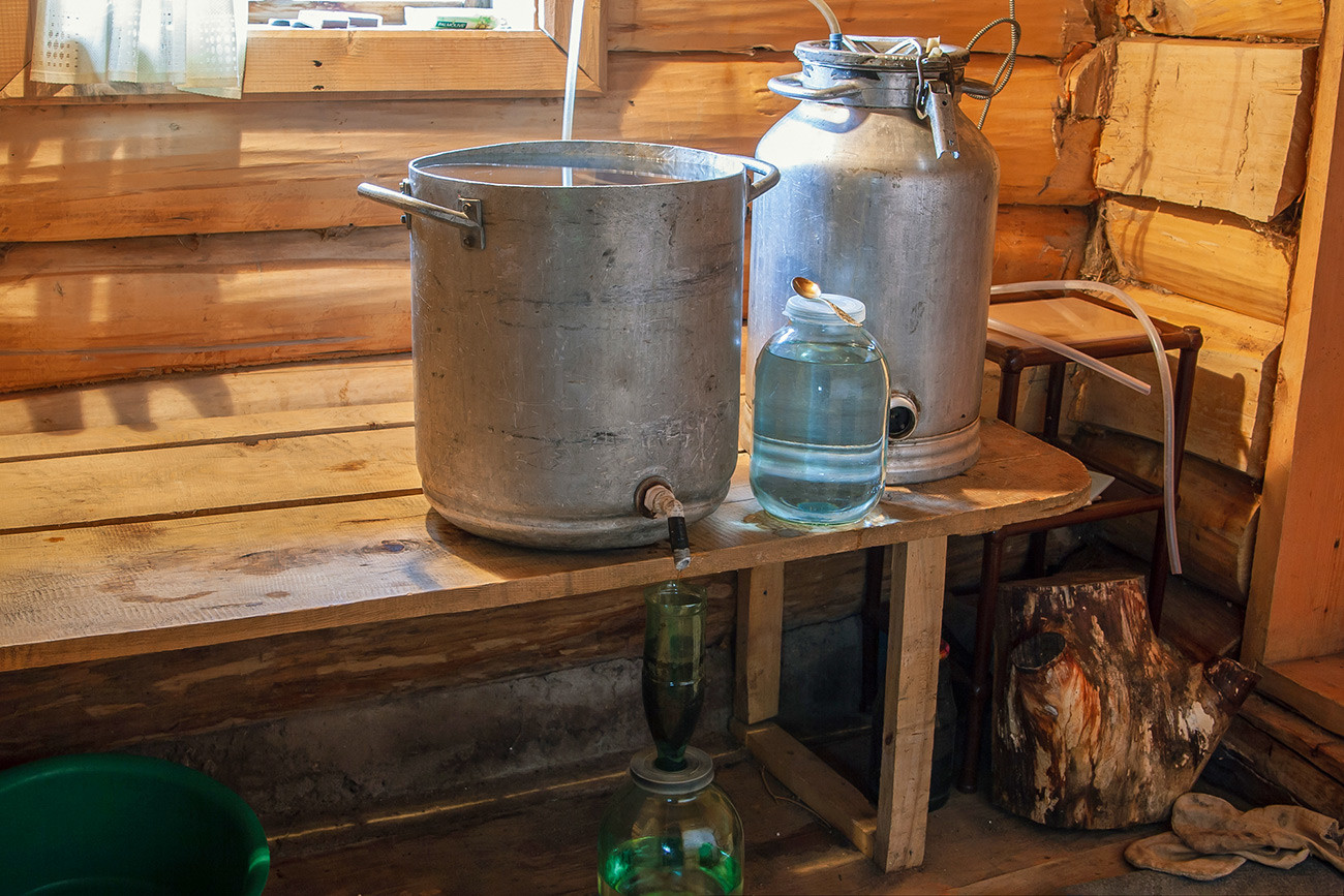 The Russian rustic way of producing alcohol in a country bath.