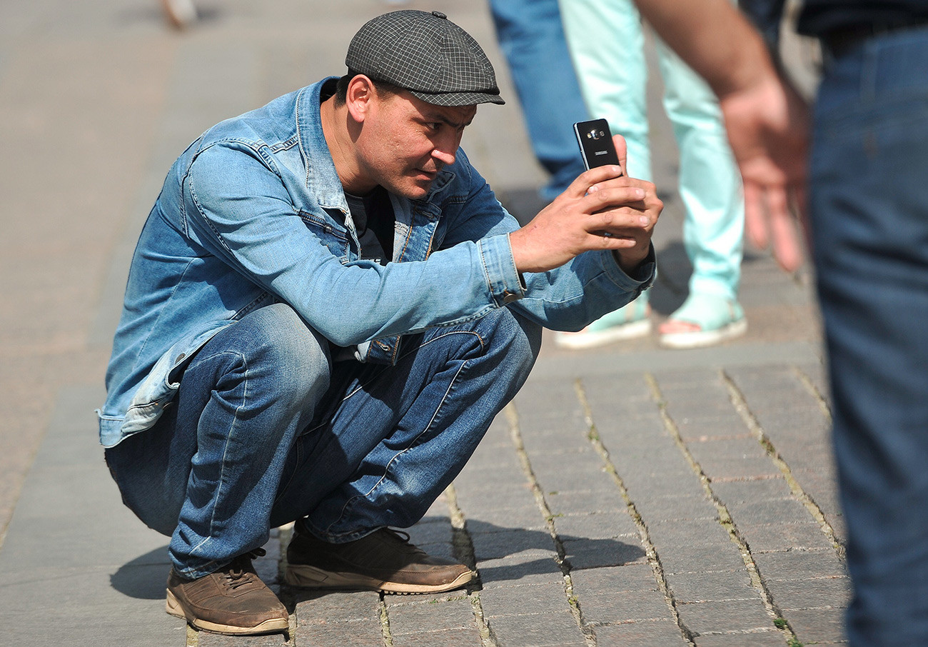 A Russian guy squats to take a picture