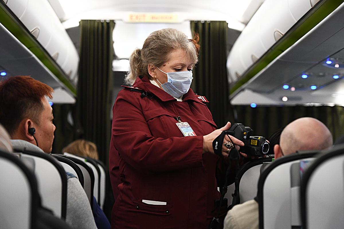 Seorang pekerja  Balai Karantina dan Sanitasi memeriksa suhu penumpang yang tiba dari Bejing dengan naik pesawat di bandara di Novosibirsk, Rusia.
