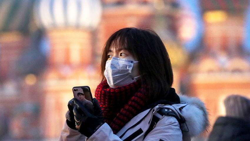 Seorang turis mengenakan masker di Lapangan Merah, Moskow, Rusia, Rabu (29/1).