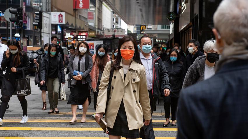 Прохожие в защитных масках на одной из улиц в Гонконге.