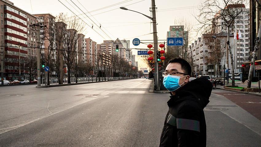 Ilustrasi: Seorang warga Tiongkok berdiri di jalanan yang sepi di Kota Beijing, baru-baru ini.