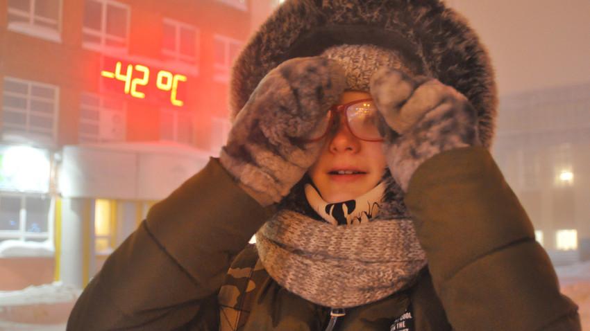 Seorang perempuan berdiri berlatarkan papan informasi suhu yang menunjukan -42 °C di Norilsk. Denis Kozhevnikov