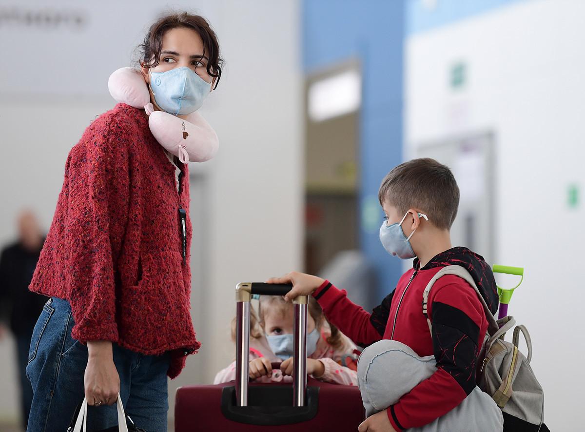 Владивисток, Русија, јануари 31, 2020 - Жена со деца во медицински маски пристигнаа од кинескиот град Сања на меѓународниот аеродром во Владивосток.