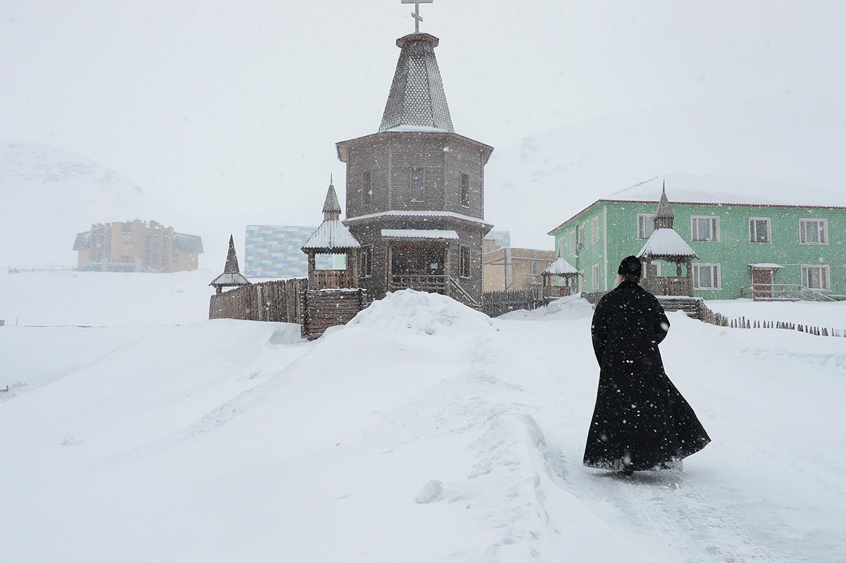 Sacerdote vicino alla chiesa di Barentsburg