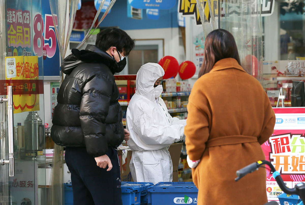 A worker in protective suit serves customers at a pharmacy following an outbreak of the new coronavirus in Wuhan.