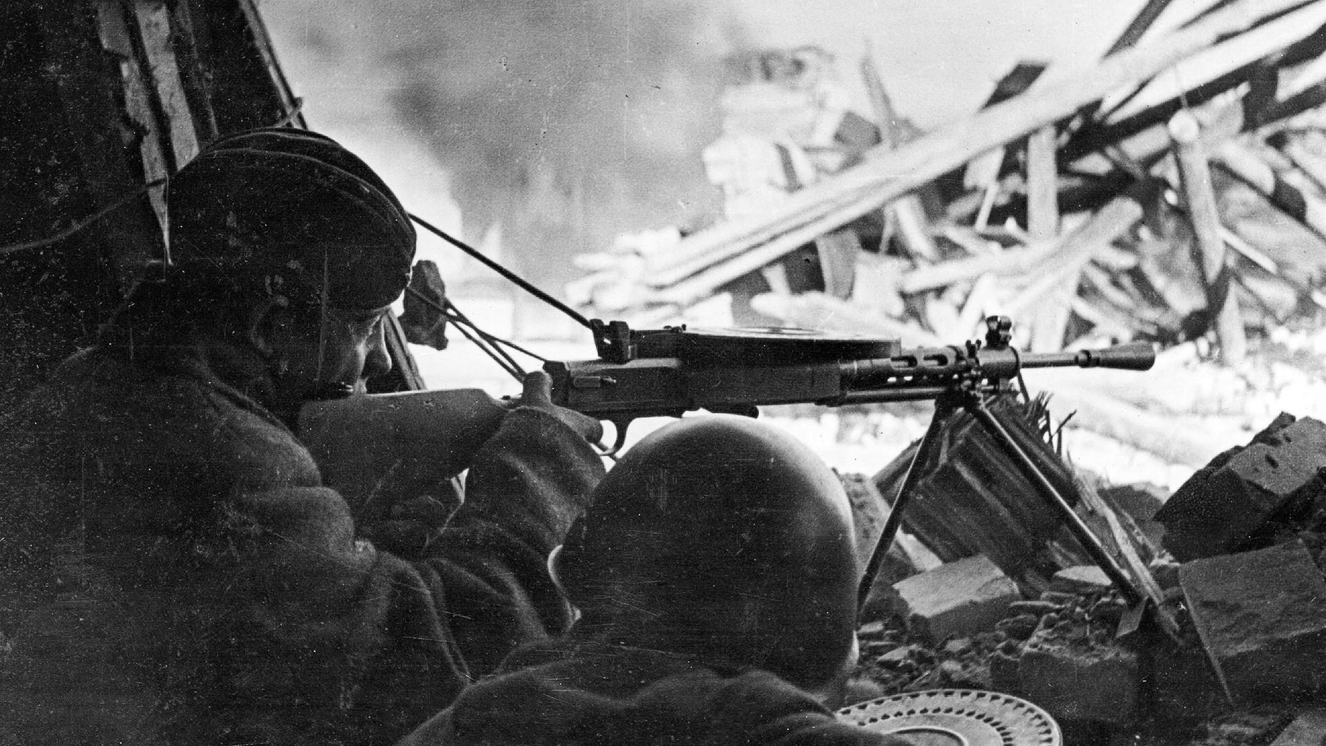 Ametralladoras soviéticas disparan contra los nazis que se habían encerrado en casas durante los enfrentamientos callejeros en las afueras de Stalingrado