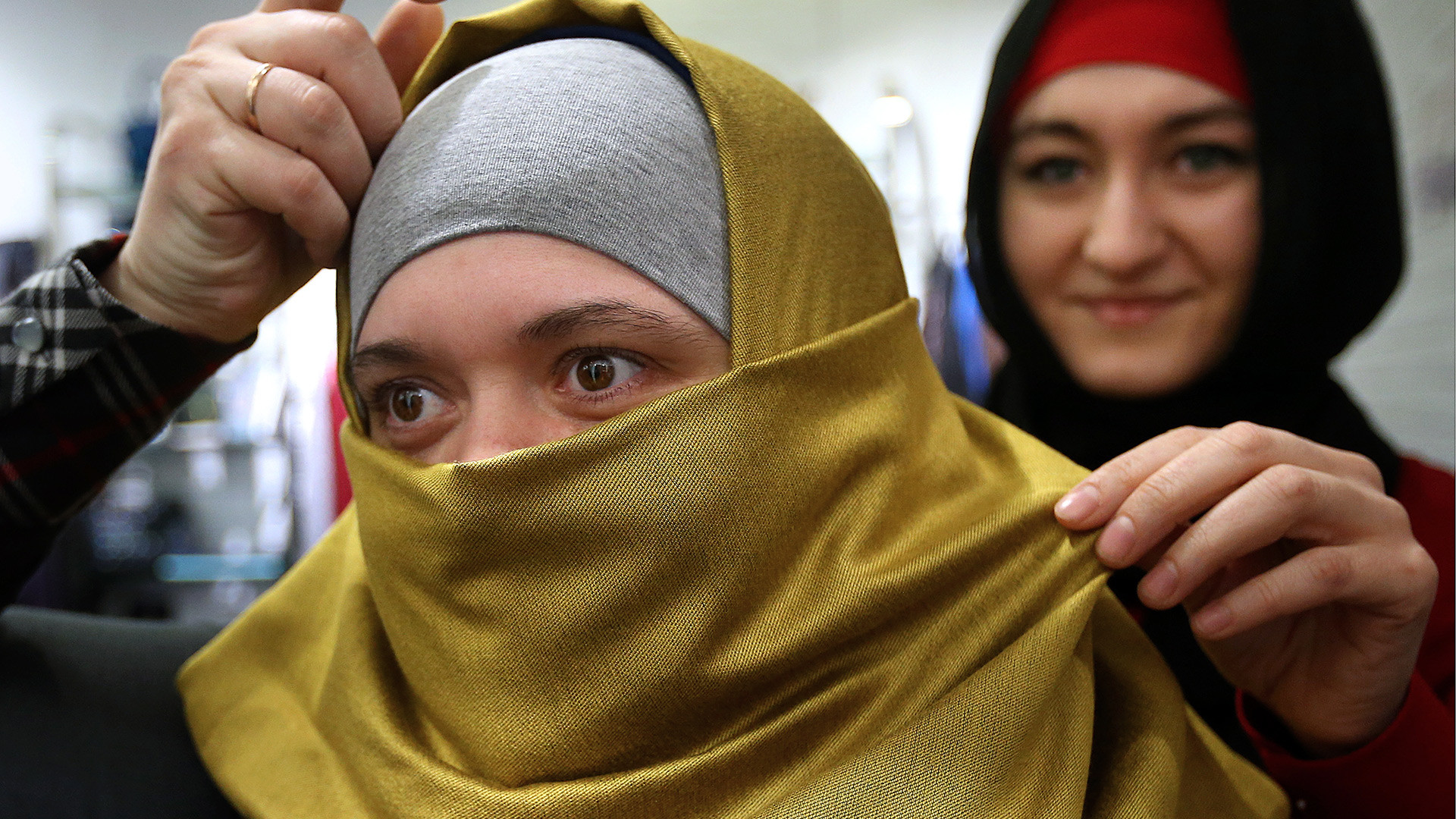 A woman chooses a hijab in a Moscow shopping center.