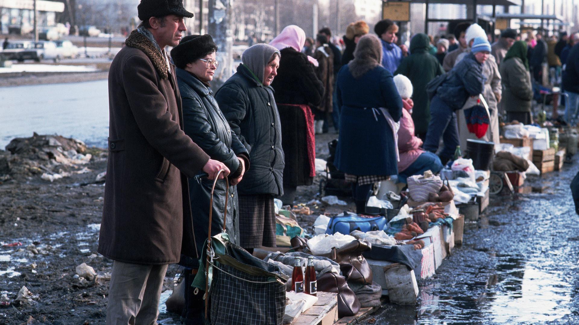 Des citoyens vendent leurs biens sur un marché installé le long d'une rue boueuse de Moscou.