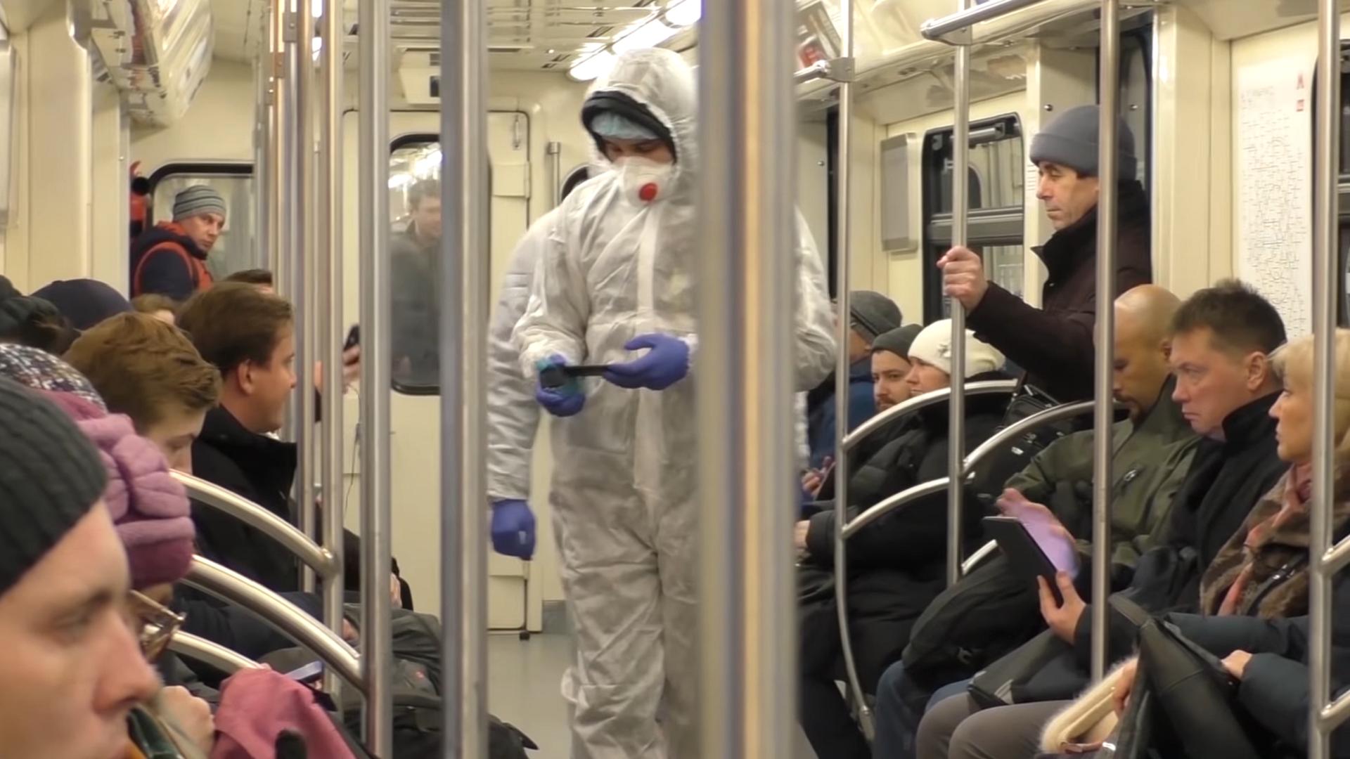 Des individus en combinaison de protection dans le métro de Moscou