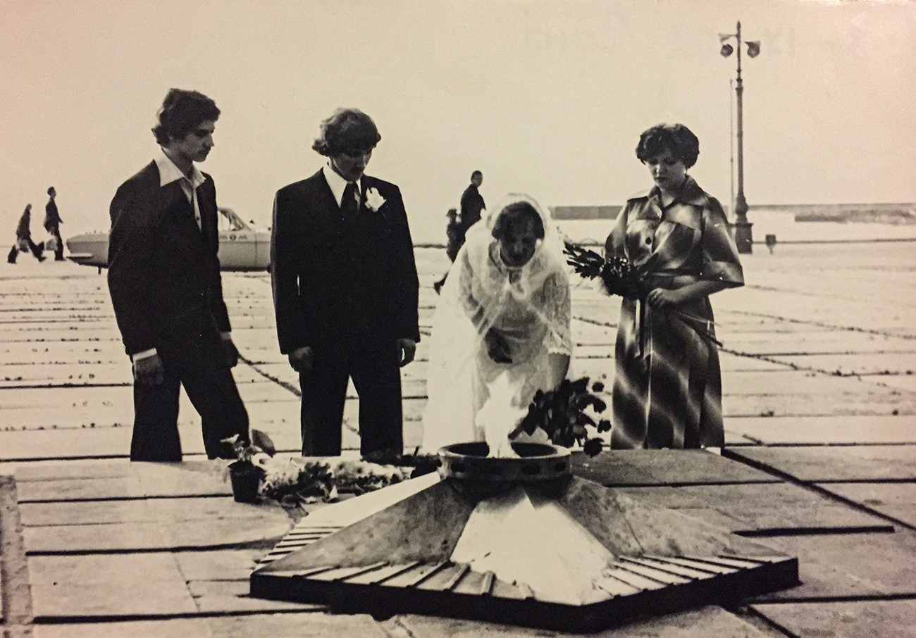 第二次世界大戦で戦ったソ連兵に捧げられる「永遠の火」の横に花を手向ける新郎新婦と証人たち。