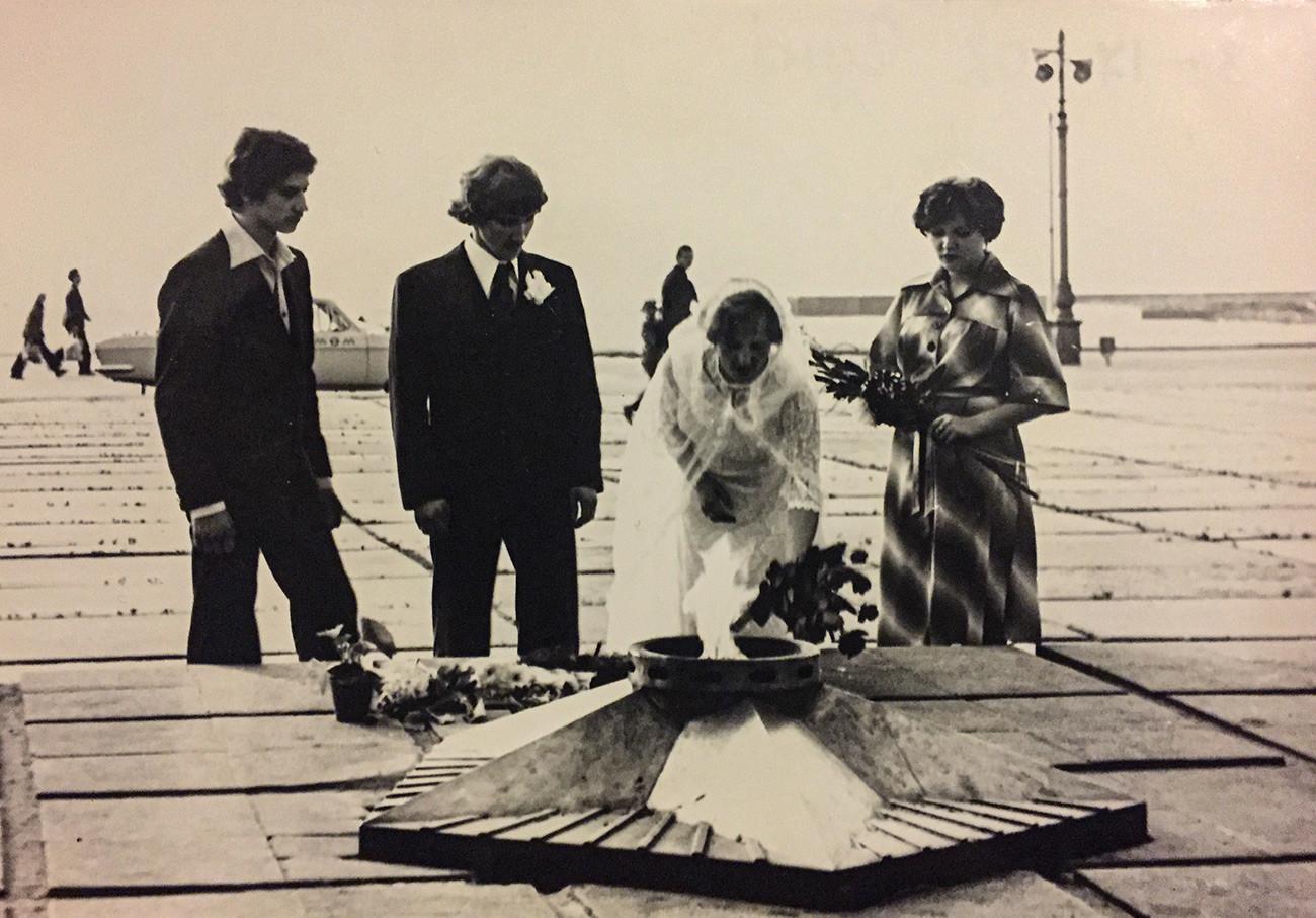 Los novios y sus testigos colocan flores junto a un monumento de la Llama inmortal dedicado a los guerreros soviéticos en la Segunda Guerra Mundial