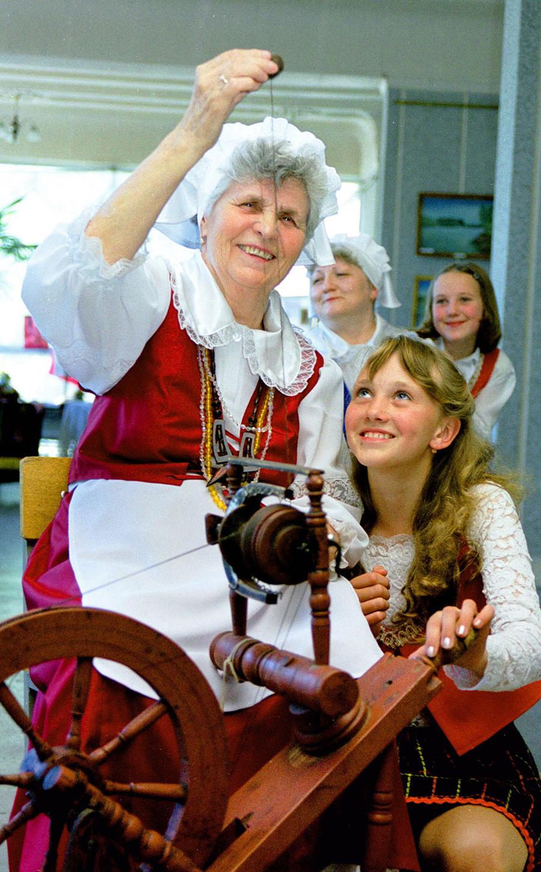 Lidia Mertes (a la izquierda) de Ekibastus le muestra a Alena Schmidt cómo usar una vieja rueca