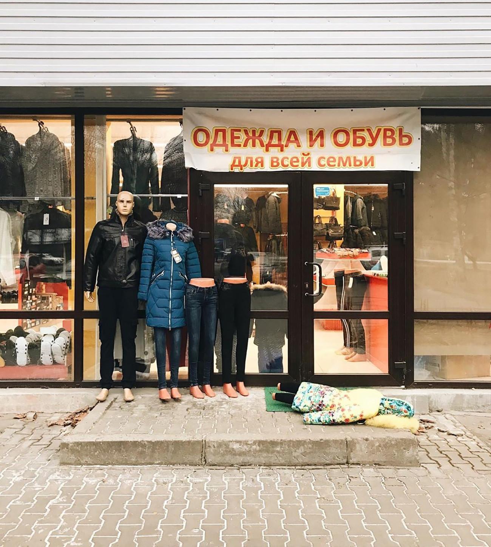 看板に書かれている文字「家族みんなのための衣服と靴」。キャプション:「家族は堂々と強くあるためのルーツを与えてくれる © Larisa Guzeyeva」。