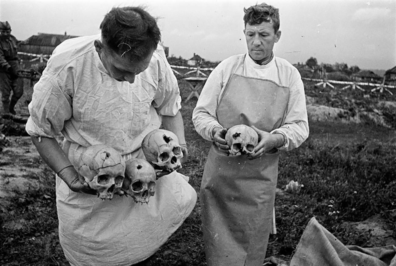 Arqueólogos forenses soviéticos estudam restos mortais de campo de concentração em 1943.